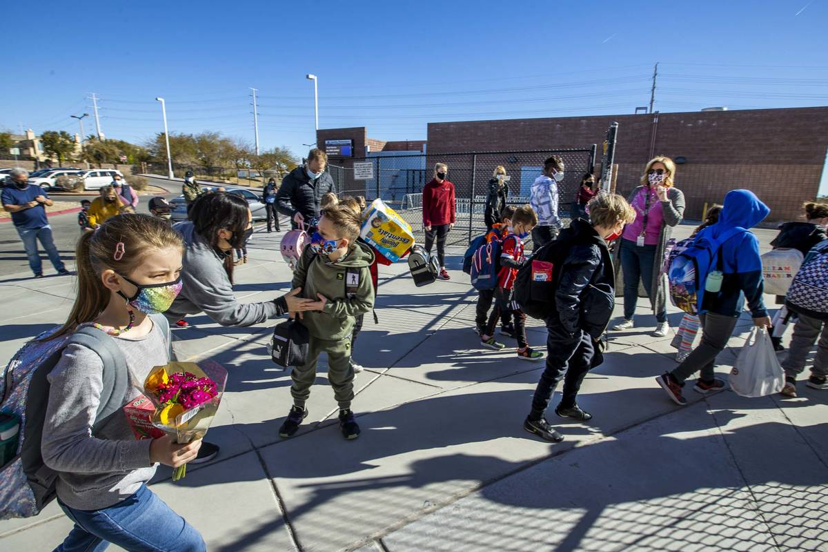 Students begin to enter a side gate at Goolsby Elementary School as they return to class on Mon ...
