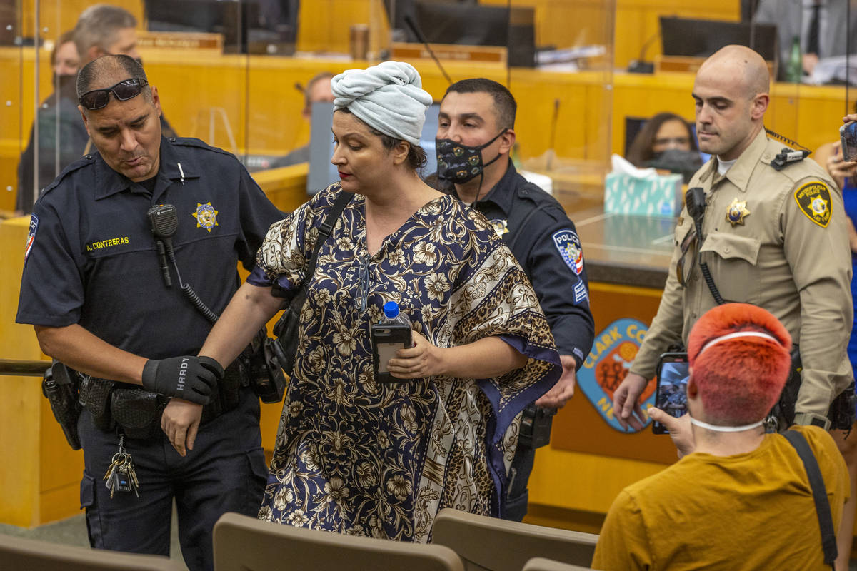 Officers escort Katrin Ivanoff from the Clark County Commission meeting for public outbursts as ...