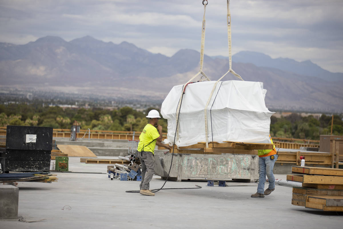 Workers move equipment on the building rooftop of the Kirk Kerkorian School of Medicine at UNLV ...