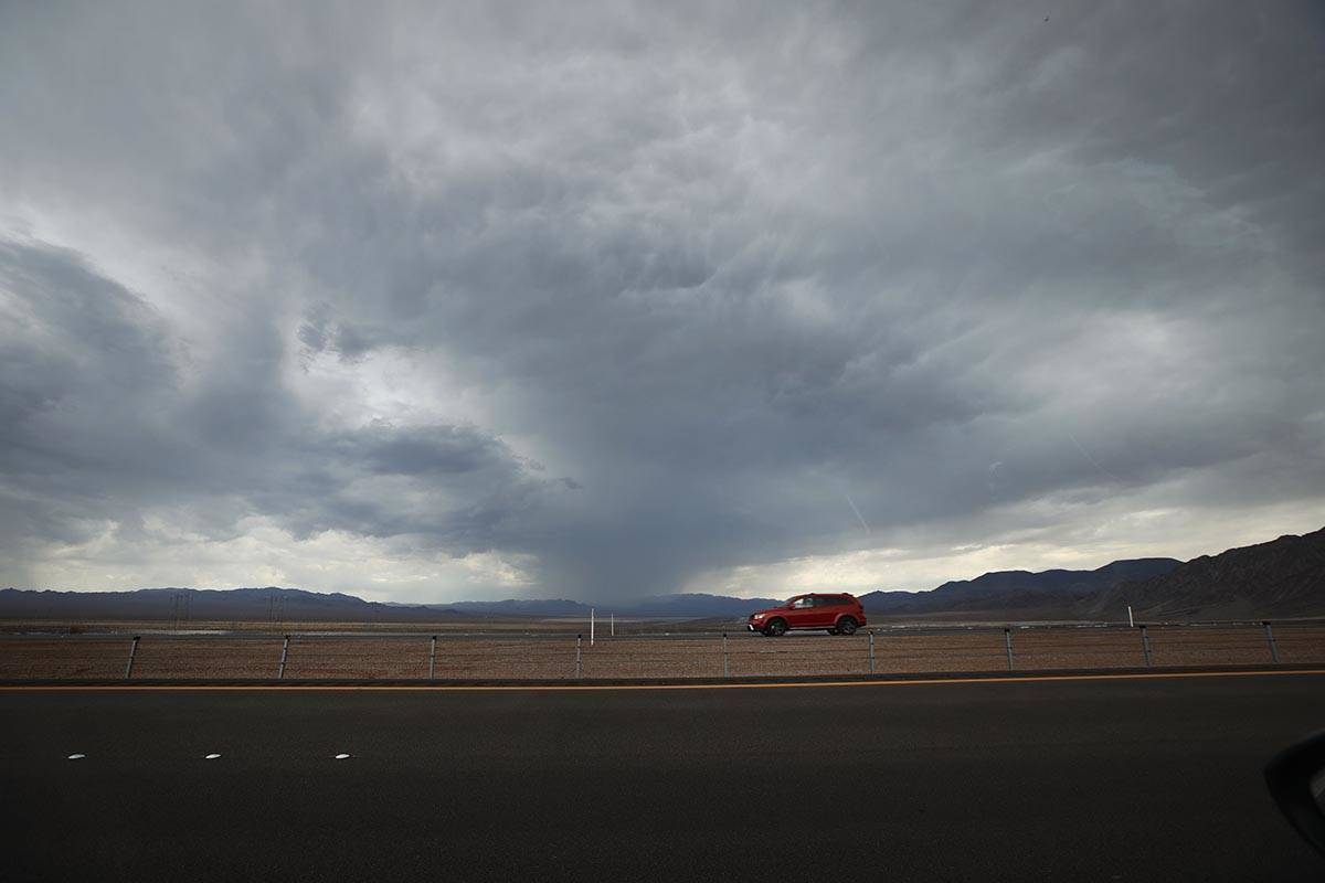 A car drives on U.S. Route 93 near Boulder City, Wednesday, July 21, 2021, as dark clouds drift ...