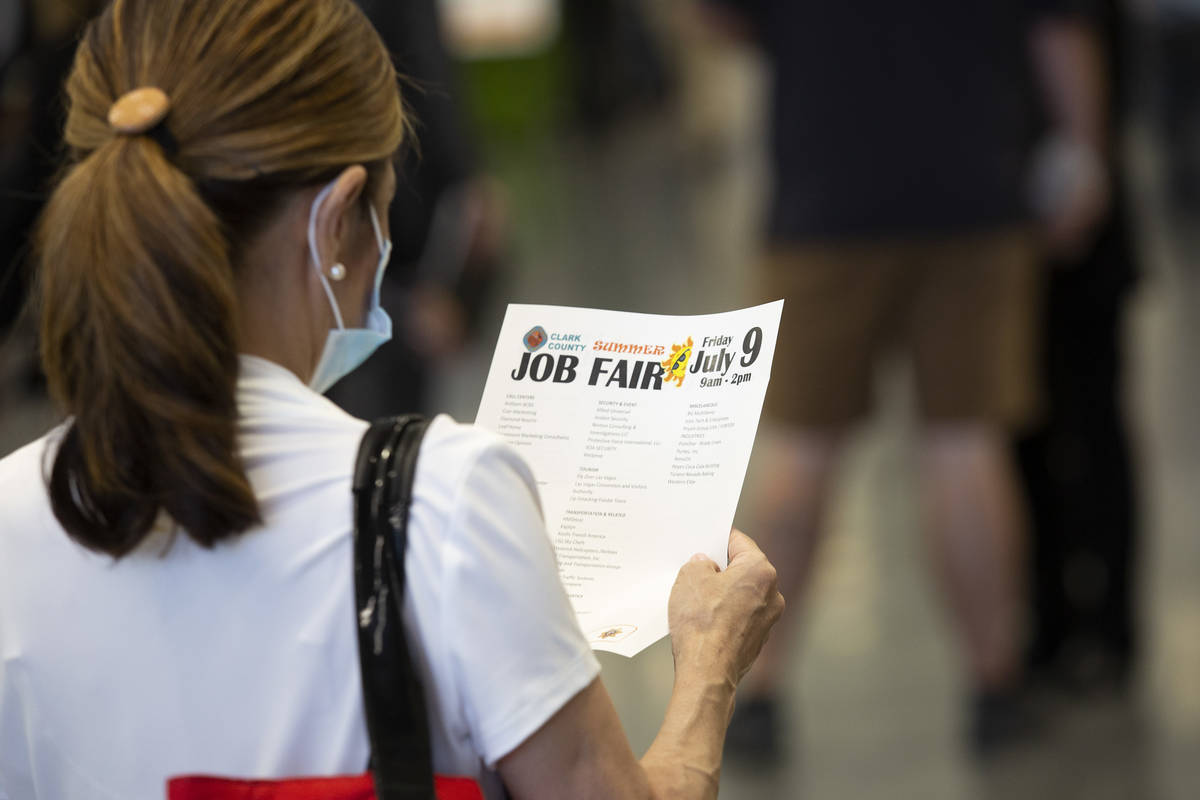 A job-seeker reviews a flyer at a summer job fair hosted by Clark County at Las Vegas Conventio ...