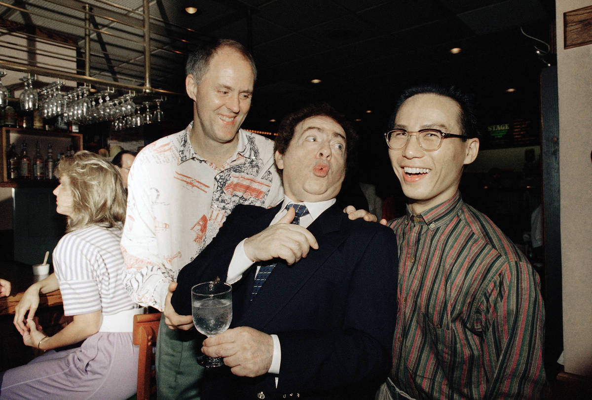 FILE - In this July 21, 1988, file photo, comedian Jackie Mason, holding a glass, enjoys a jok ...