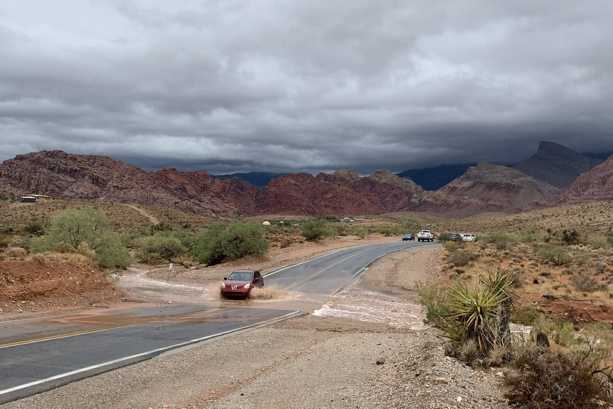 A car crosses flood water on Calico Basin Road in western Las Vega. (David Guzman/Las Vegas Rev ...