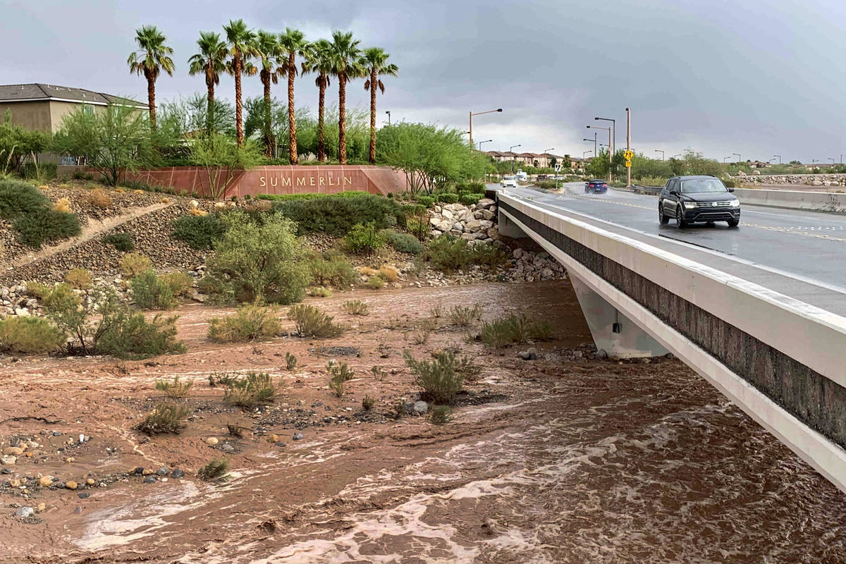 Flood waters flow beneath Charleston Boulevard near Red Rock Canyon National Conservation Area ...