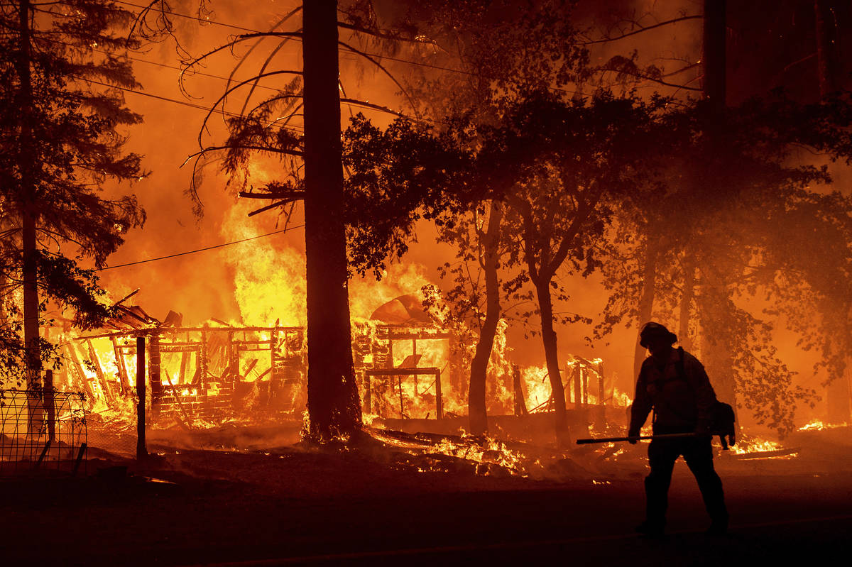 A firefighter passes a burning home as the Dixie Fire flares in Plumas County, Calif., Saturday ...