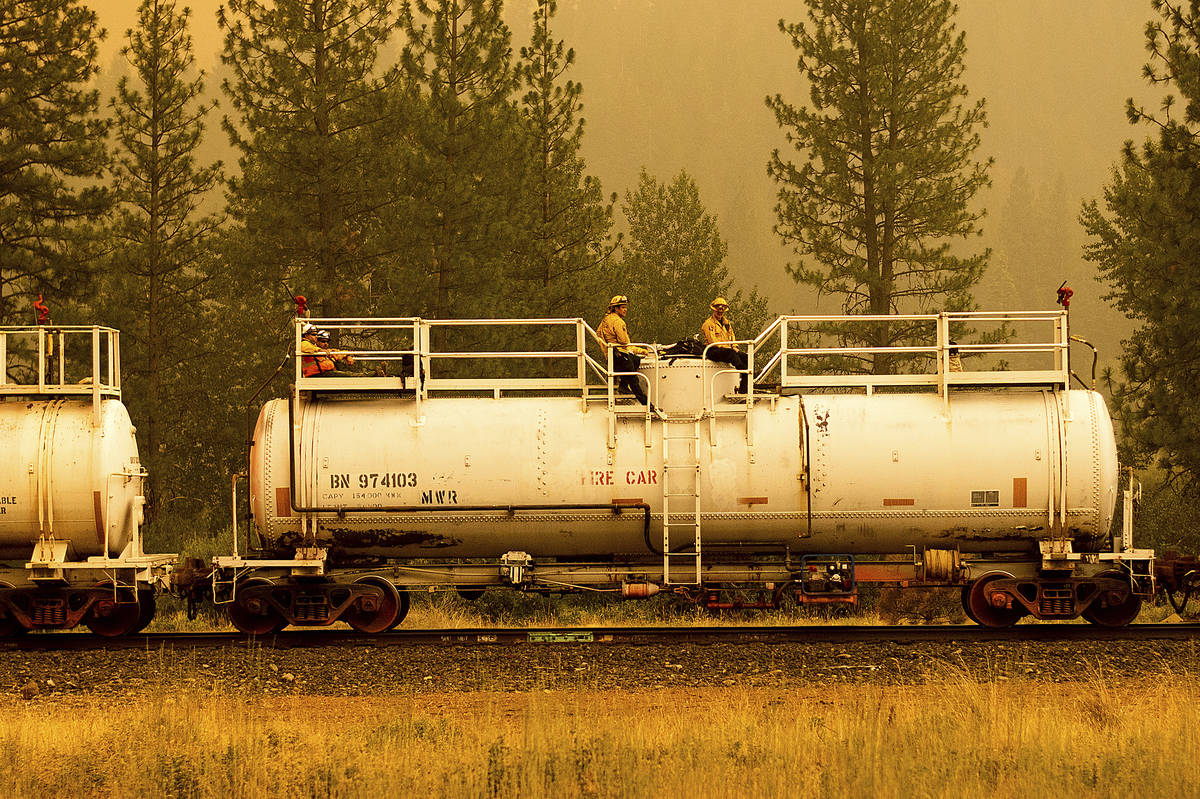 Firefighters ride atop a fire train while battling the Dixie Fire in Plumas County, Calif., on ...