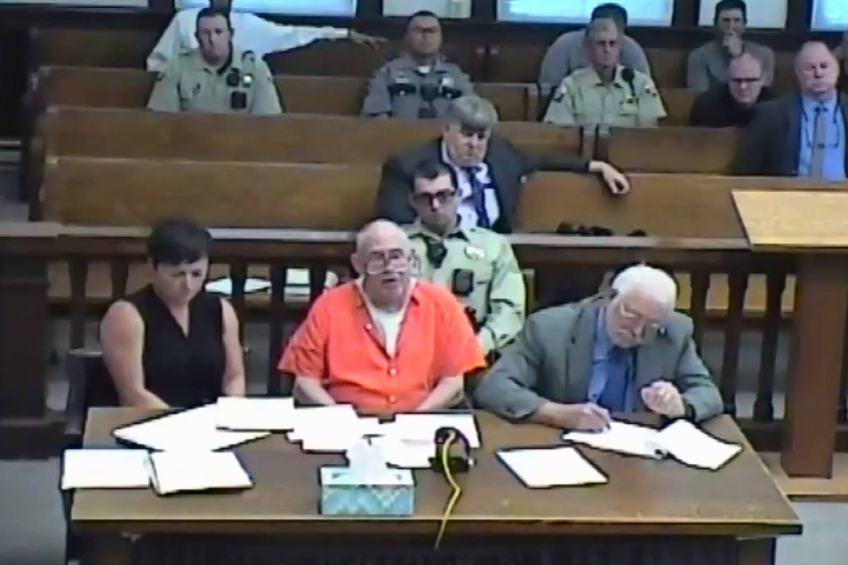 In this screenshot of a livestreamed court hearing, John Dabritz, center, is pictured alongside ...