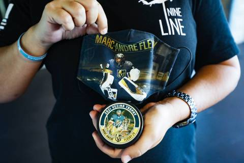 Tonya Fabian holds a puck and mask featuring Golden Knights goaltender Marc-Andre Fleury who wa ...