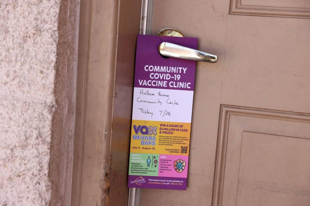 A door hanger announcing a FEMA surge team COVID-19 vaccination event at Hullum Homes public ho ...