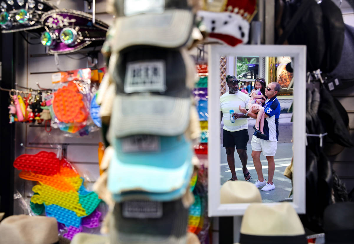Visitors walk under the Fremont Street Experience in Downtown Las Vegas Wednesday, July 28, 202 ...