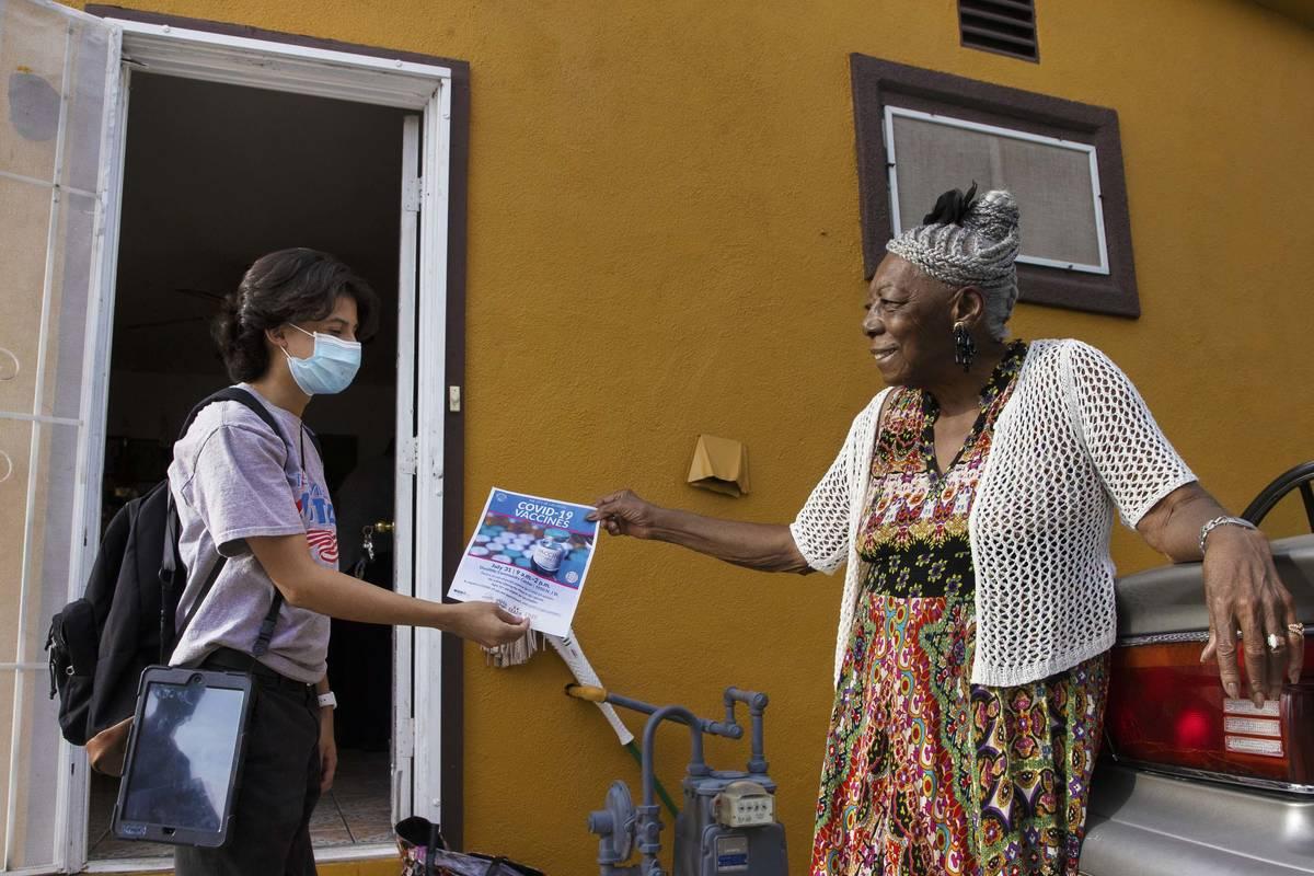 Jacinto Alfaro, left, a volunteer with the nonprofit Mi Familia Vota, hands a COVID-19 vaccine ...