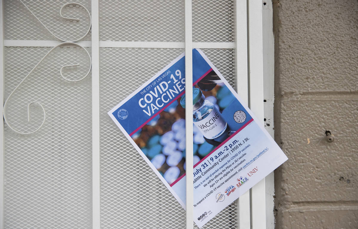 A COVID-19 vaccine information flyer placed on the door at an apartment complex by nonprofit vo ...