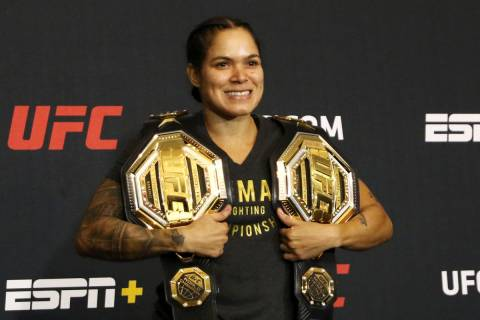 UFC women's bantamweight and featherweight champion Amanda Nunes poses with her belts during a ...