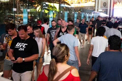 People cross the pedestrian bridge between New York-New York and the MGM Grand, on Saturday, Ju ...