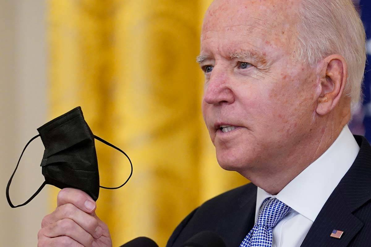 President Joe Biden holds up his face mask as he speaks about vaccine requirements for federal ...