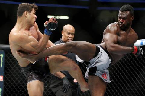 Paulo Costa, left, and Uriah Hall exchange kicks in the middleweight bout during UFC 226 at T-M ...