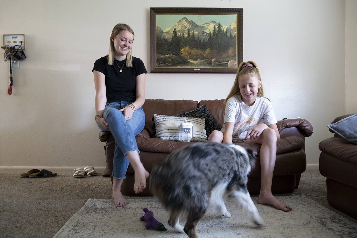Kylee Tobler and her little sister, Anni, play with her dog, Benny, in the living room of her B ...