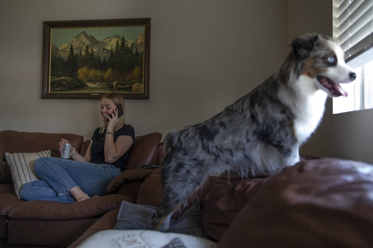 Kylee Tobler speaks with her mom on the phone while her dog, Benny, looks out the living room w ...