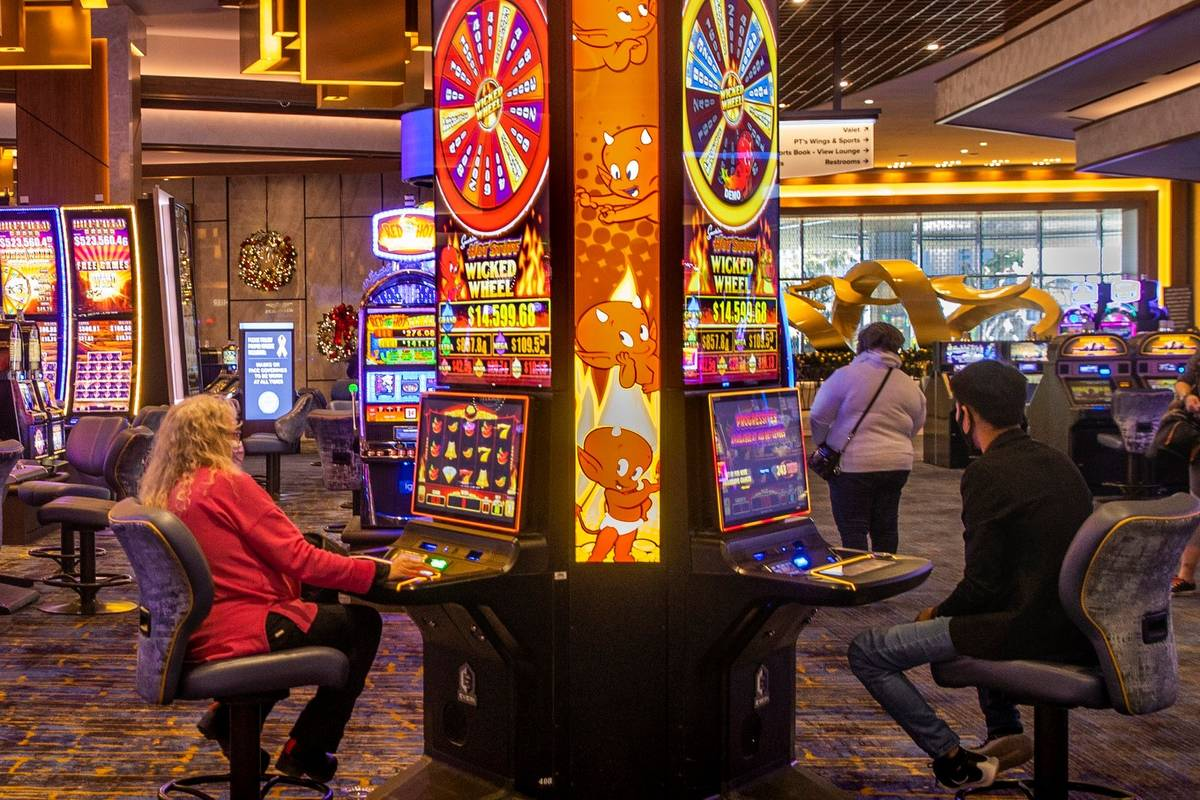 A few slot machines are played on the casino floor at the Strat in December 2020 in Las Vegas. ...
