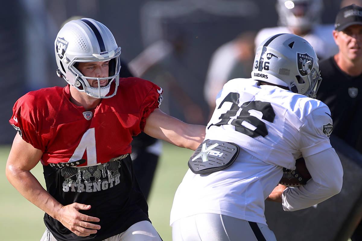Las Vegas Raiders quarterback Derek Carr (4) hands off the ball to running back Trey Ragas (36) ...