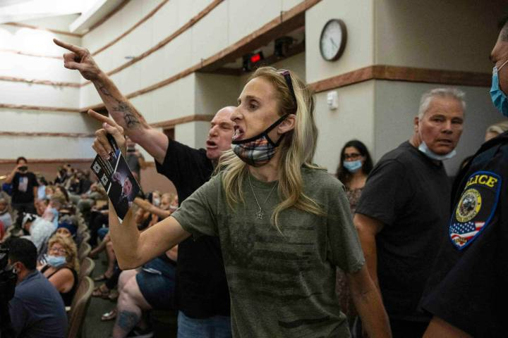 Protesters against a COVID-19 mandate gesture as they were escorted out of the Clark County Sch ...