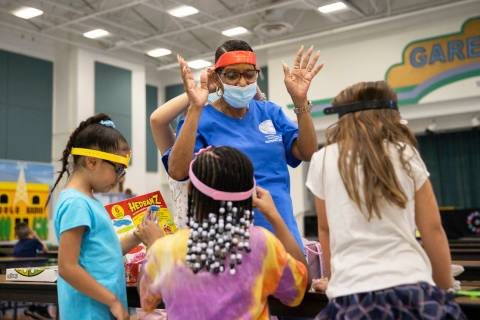 Safekey assistant site lead Troye Boudreaux, top/middle, plays a game with children at Garehime ...