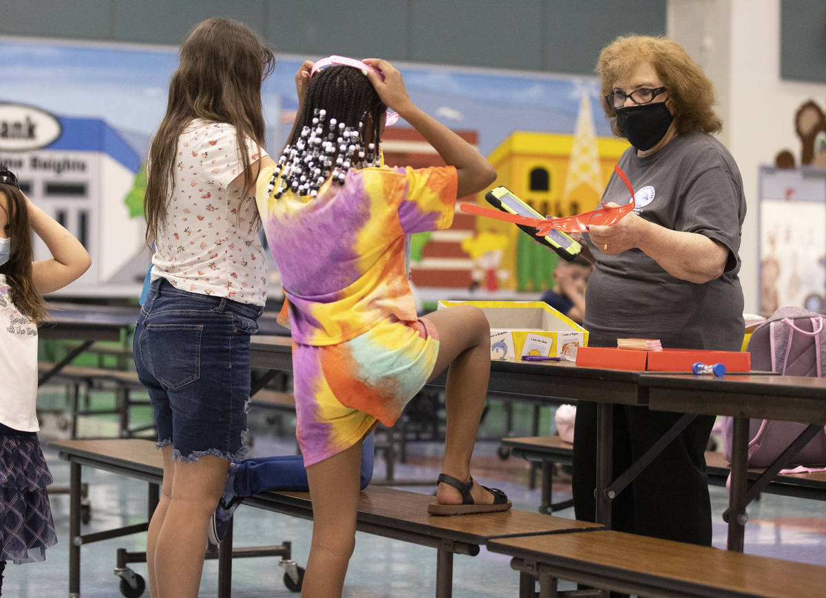 Safekey site lead Marge Galioto, right, plays a game with children at Garehime Elementary Schoo ...