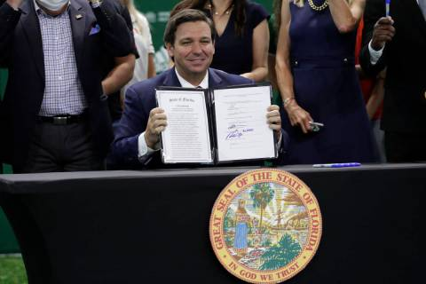 Florida Gov. Ron DeSantis holds up a just signed bill which would allow college athletes in the ...