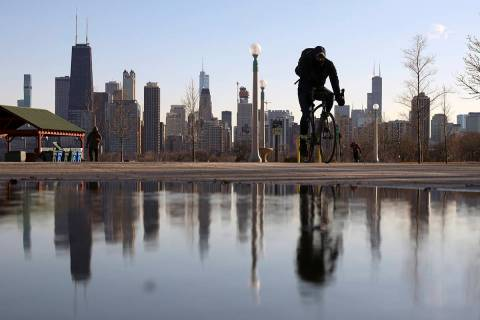 The Chicago skyline is reflected in the water of the thawed snow as a cyclist passes by at Nort ...