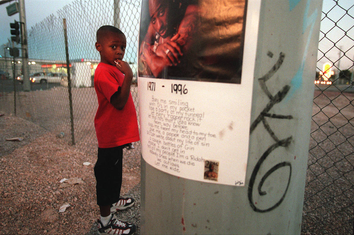 Kiondre Pollard, 6, stands next to a poster of Tupac Shakur before a vigil honoring the late hi ...