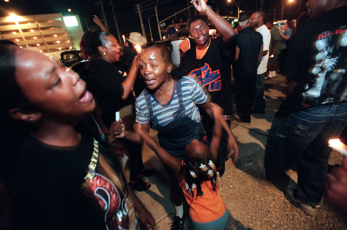 Fans dance during a candlelight vigil Sunday night on the second anniversary of the death of Tu ...