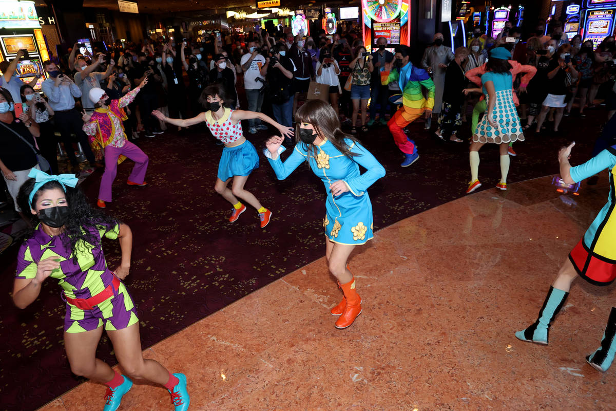 The cast of The Beatles LOVE entertain guests, employees, and fans during a celebratory pop-up ...