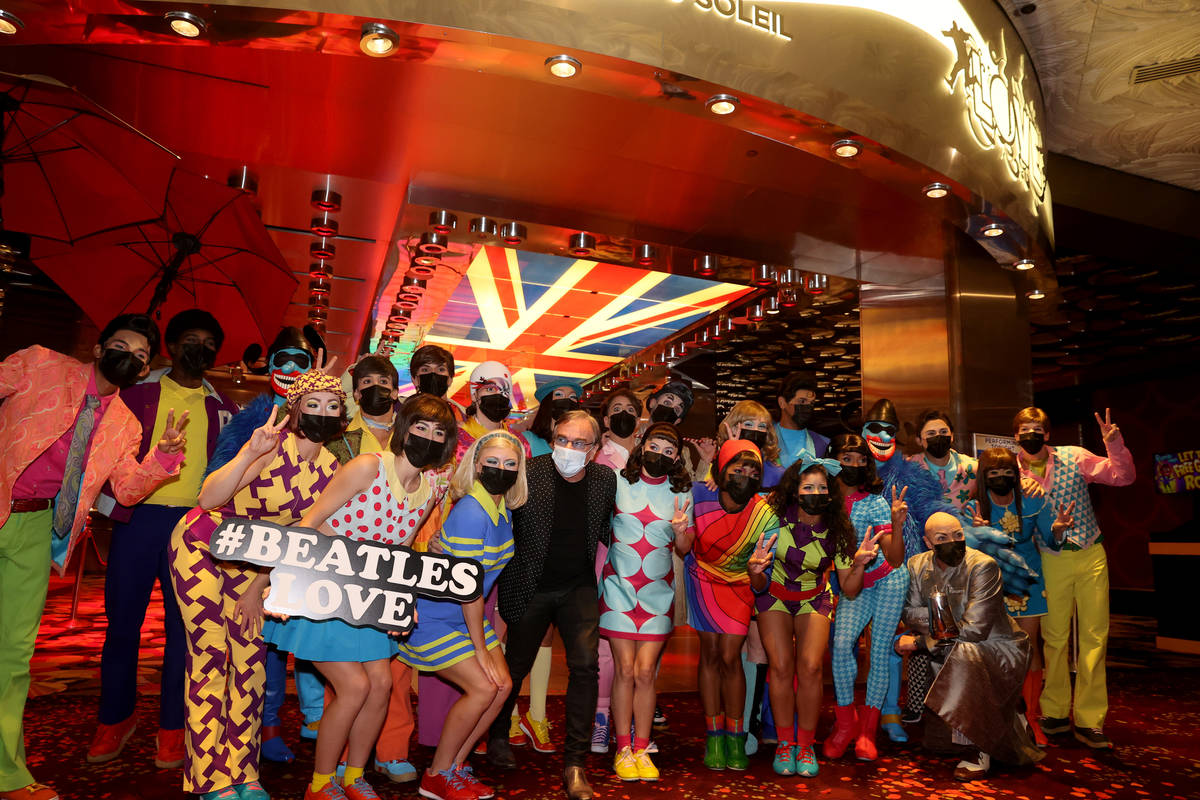 The cast of The Beatles LOVE, including Daniel Lamarre, president and CEO, center, entertain gu ...