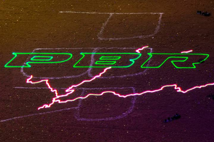 A PBR logo with lightning projected on the dirt ring during the last day of the PBR World Final ...