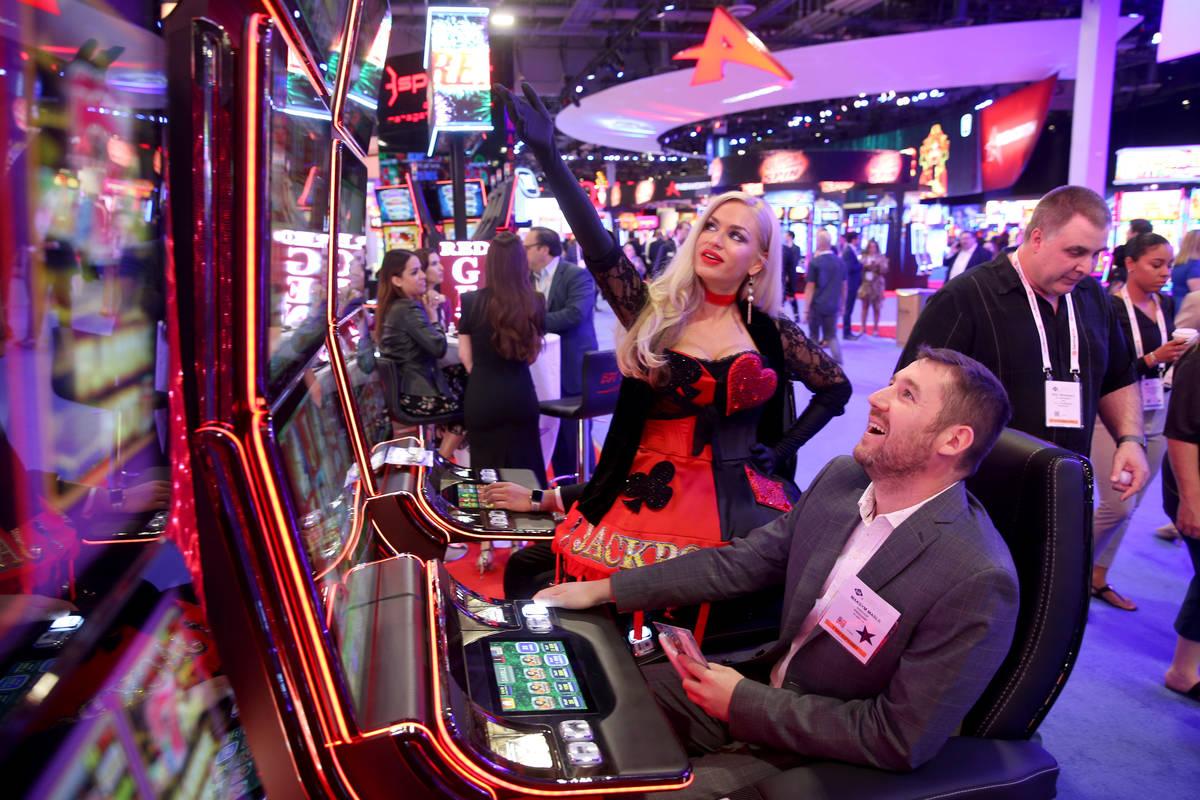 Joyce Jones of Las Vegas shows Maksym Maslii, of Digicode of Plano, Texas, how to play Jackpot ...