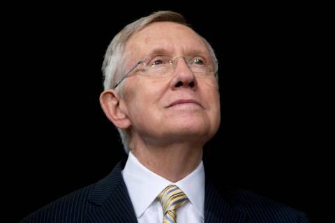 Senate Majority Leader Harry Reid of Nevada looks to President Barack Obama as he speaks about ...