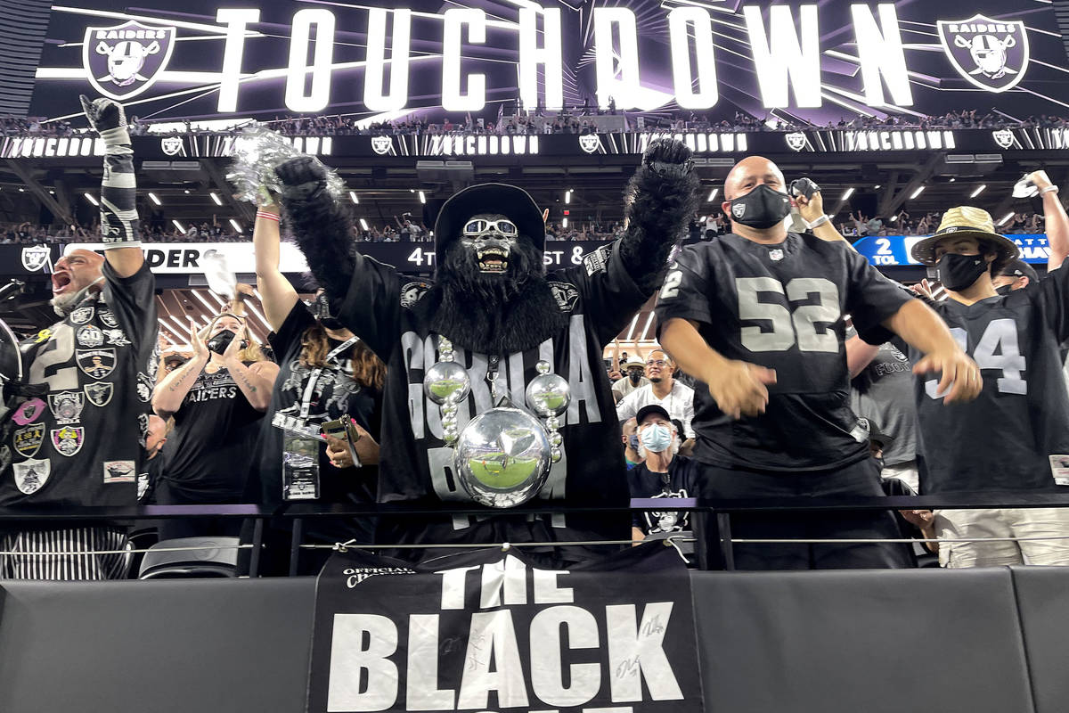 Fans, including Mark Acasio as Gorilla Rilla cheer a touchdown during the Raiders home opening ...