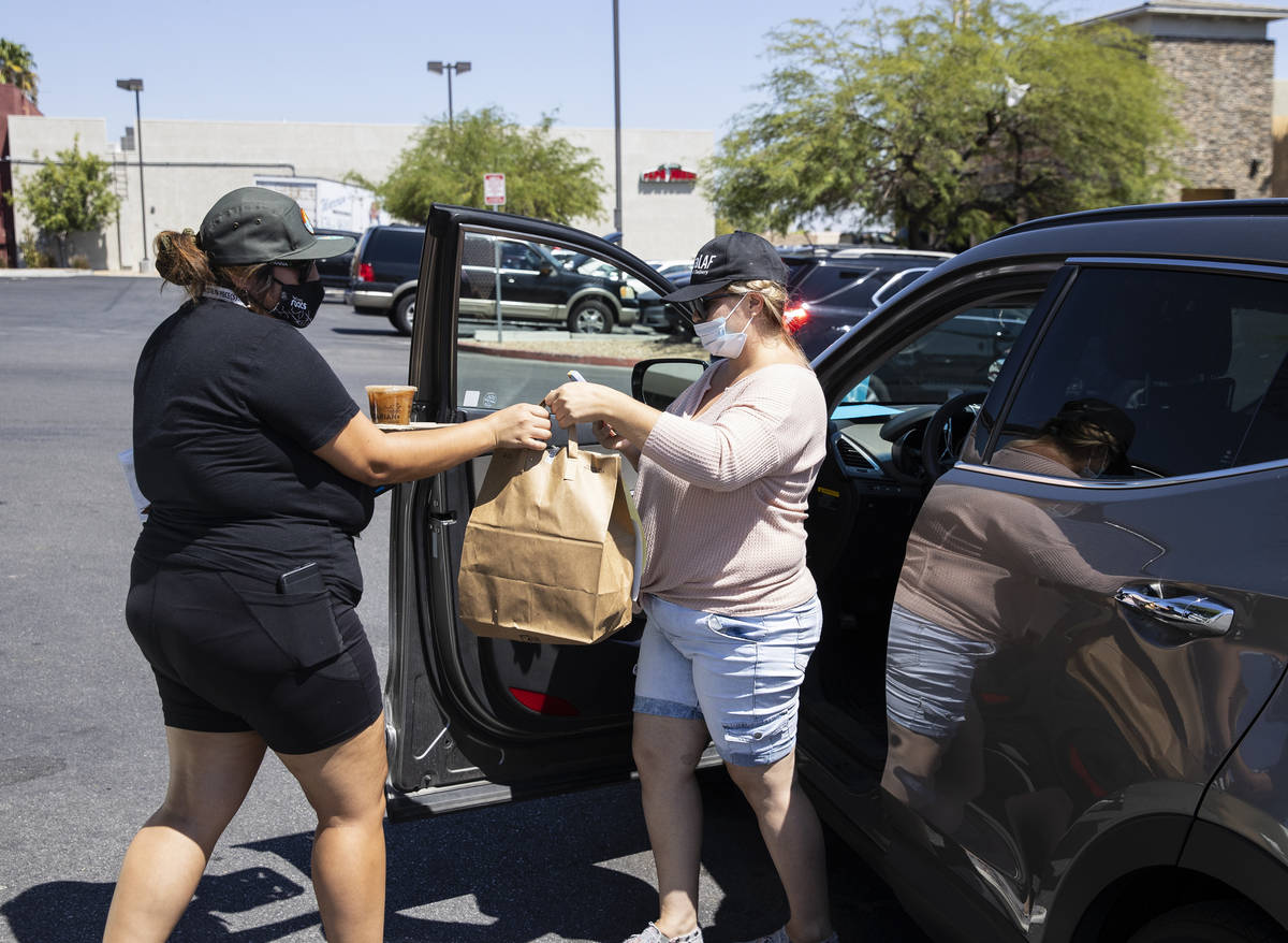 Michelle English, right, a delivery driver for Loco Co-Op, delivers food to ShowGrow Dispensary ...