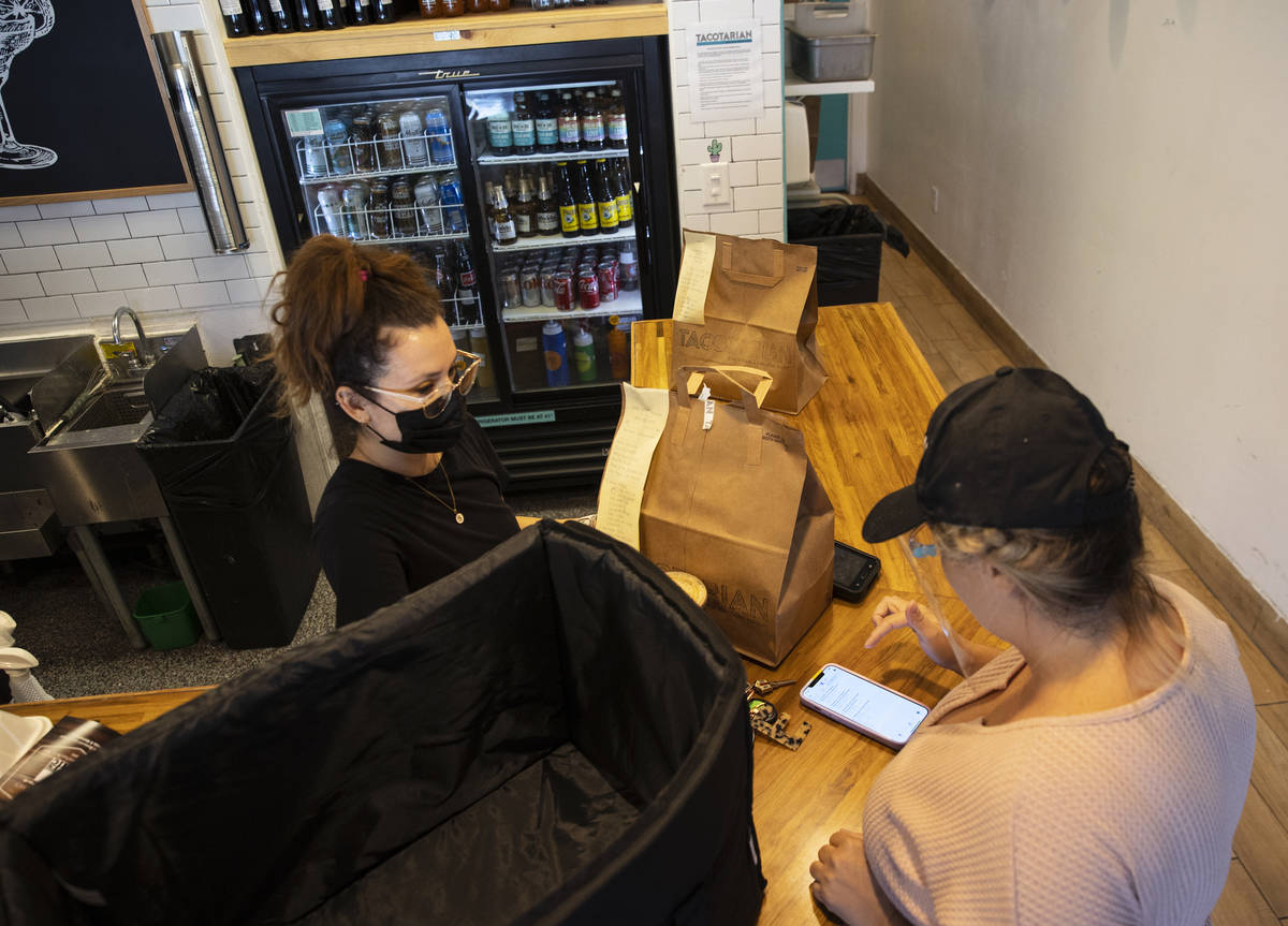 Sandra Ruiz, left, Tacotarian manager, checks out customers order as Michelle English, a delive ...