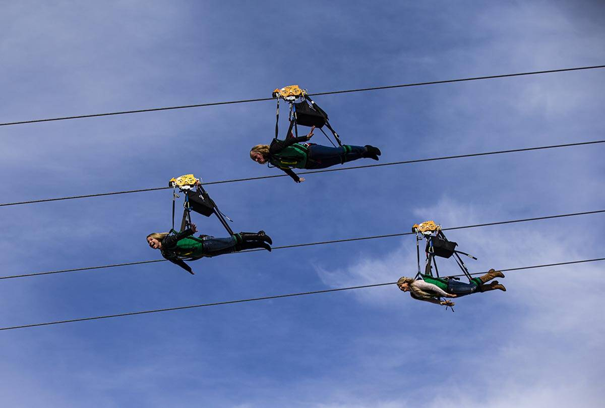 People react as they take off on the Slotzilla zip line over Fremont Street in downtown Las Veg ...