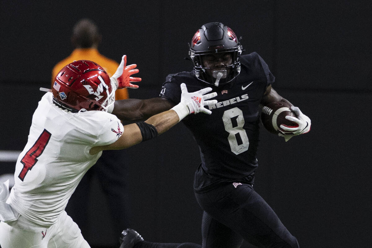 UNLV Rebels running back Charles Williams (8) fends off a tackle attempt by Eastern Washington ...