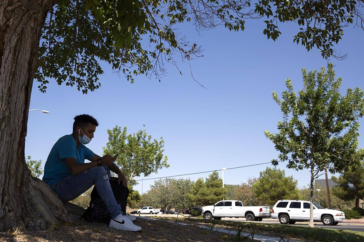 Bryan Vargas, a freshman at Rancho High School, takes refuge in the shade while waiting for the ...