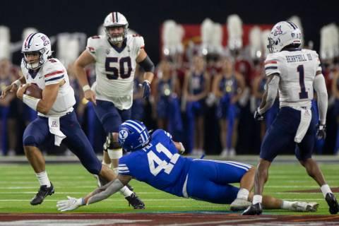 Arizona Wildcats quarterback Gunner Cruz scrambles past Brigham Young Cougars linebacker Keenan ...