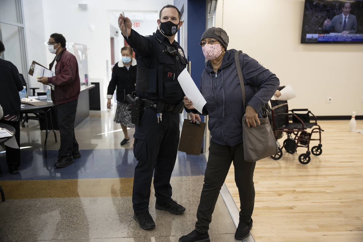 North Las Vegas Police officer Mazar directs Jacqueline Perkins-Denmark to the COVID-19 vaccina ...