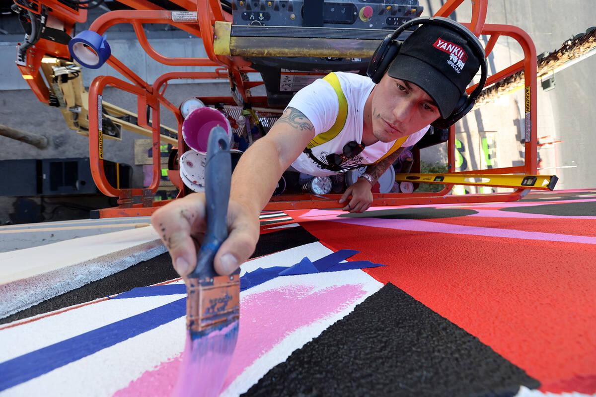 "Sasha Rayevskiy, who goes by the name ""Tigersasha,"" works on a mural by Criola titled ""Black Gi ..."