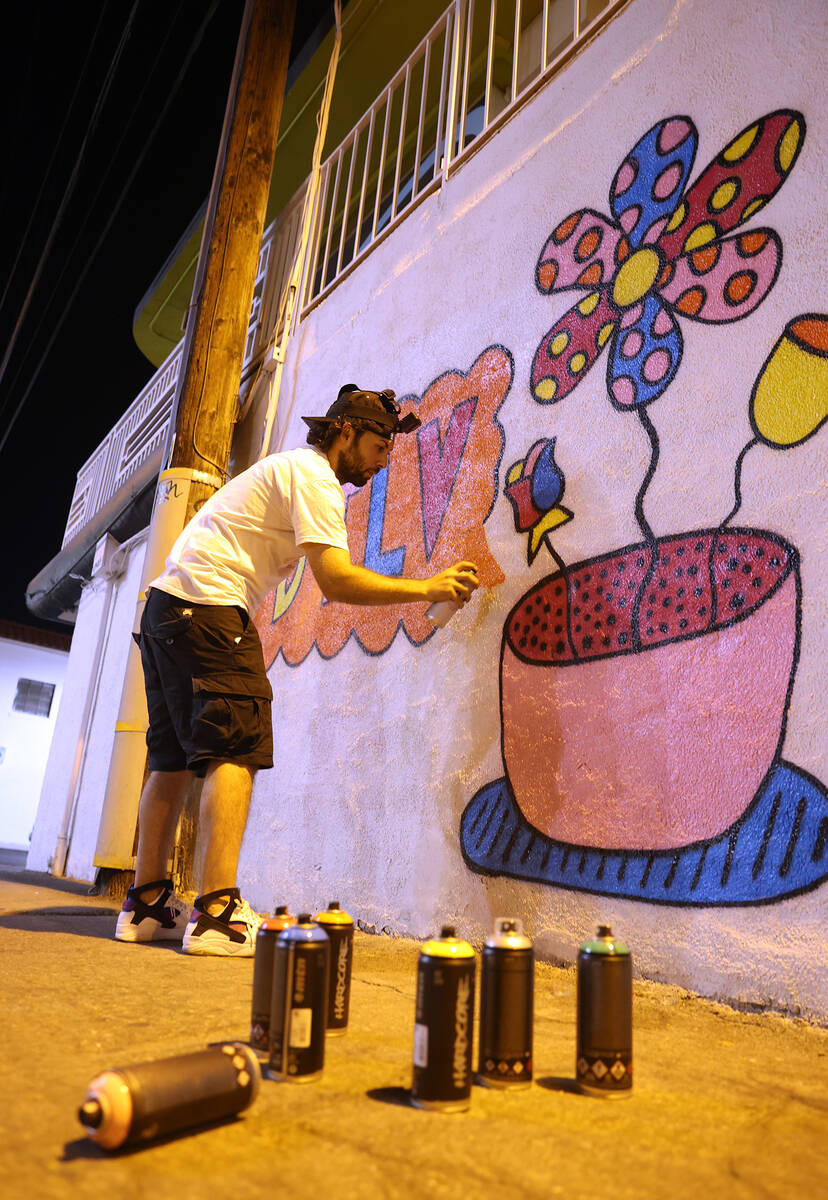 """An artist who goes by the name """"Pretty Done"""" works on his mural titled """"Pretty Funk Alley"""" for ..."""