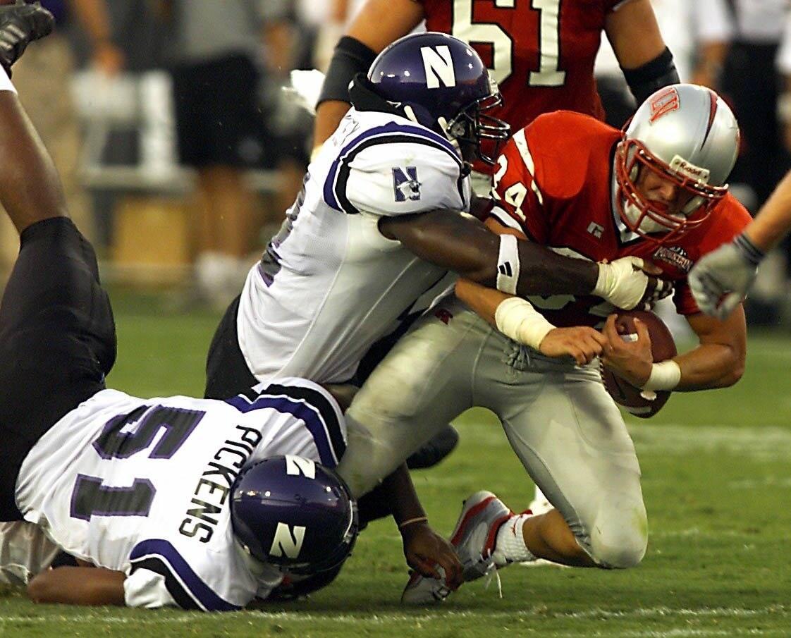SPORTS -- UNLV junior runningback Joe Haro (34) gets taken down by Northwestern senior lineback ...