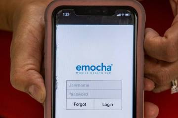 Clark County Education Association President Marie Neisess shows the emocha app on her phone in ...
