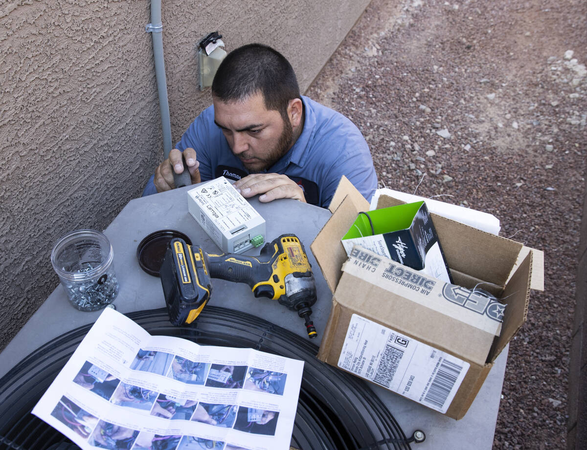 Windy City Air's technician Thomas Padron installs a soft starter as he repairs an air conditio ...