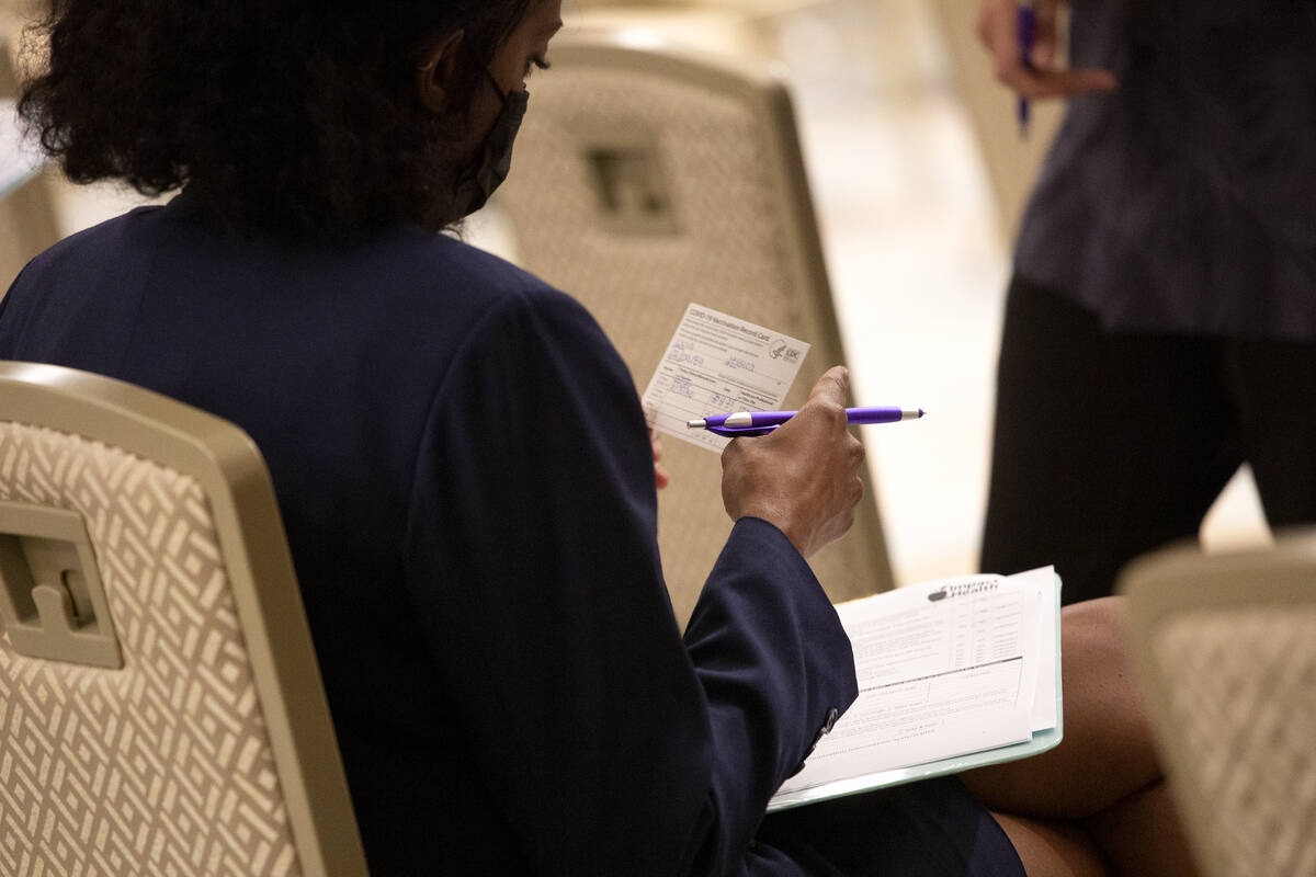 Jessica Dula reviews her vaccination card during a COVID-19 vaccine clinic at Resorts World Las ...